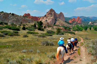 Four people on horseback riding down a trail surrounded by a green valley and rocky outcroppings amidst blue skies