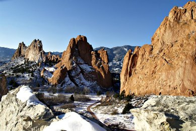 snow covered canyon with large rock formations against a clear blue sky