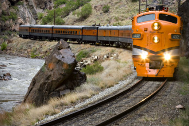 Orange and gray rail train coming around the bend with rapid water on one side and steeps on the other