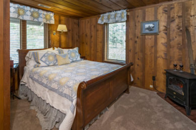 rustic wood panelled bedroom with large wooden sleighbed with white, soft gray and yellow linens in front