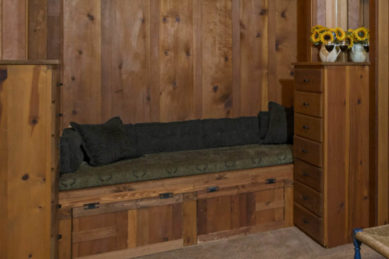 large wodden alcove couch with dark green pillows and lighter green seat cusion against rustic pine walls
