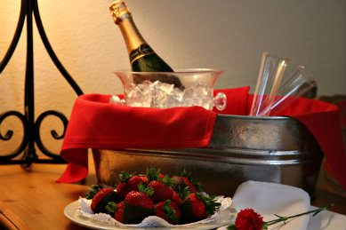 large metal bucket of ice with red linen napkin, bottle of champagne on ice, glass flutes with plate of chocolate covered strawberries in frontnd
