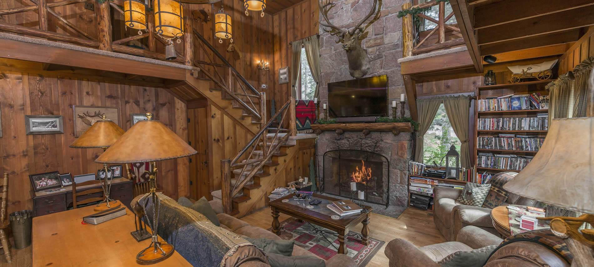 Two story wood paneled living room filled with book lined shelves, upholstered furniture and a roaring fire in stone fireplace.