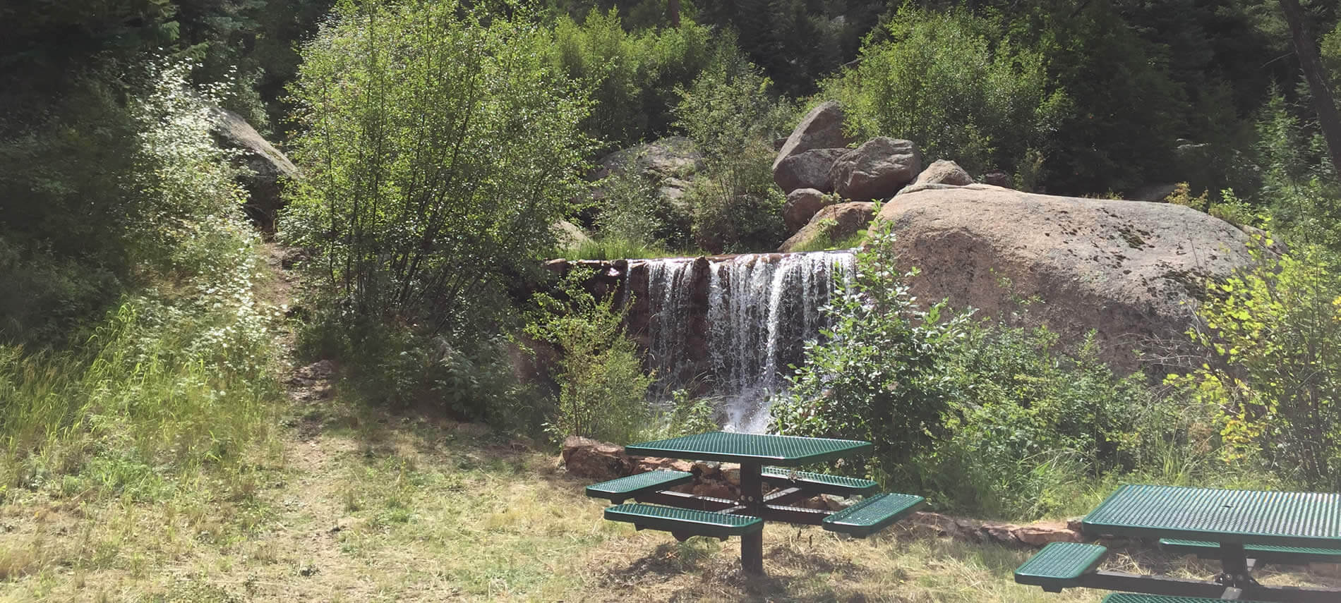 Green picnic tables near a small waterfall surrounded by boulders and greenery.