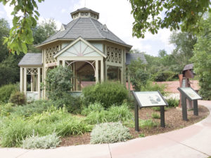 Gazebo with mineral spring water flowing inside and green bushes and trees around gazebo