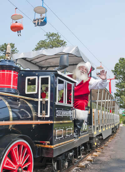 Man dressed as Santa Claus sitting in a black and red train
