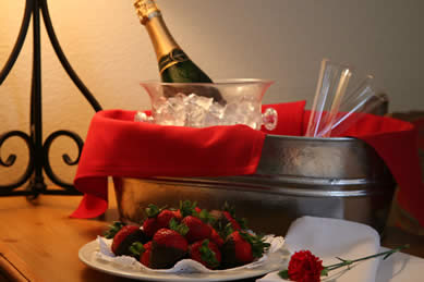 Silver metal bucked filled with ice, champagne and two flutes on a table near a plate of chocolate dipped strawberries