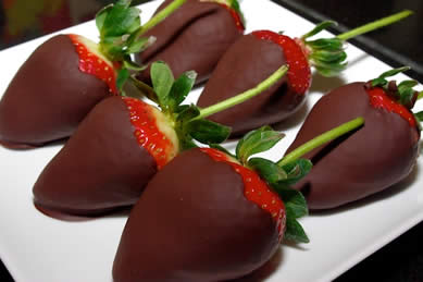 White plate topped with bright red strawberries with green stems dipped in chocolate