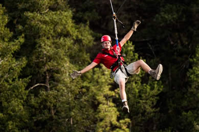 man with arms outstretched zip lining above tall gree trees