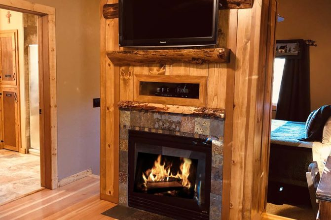 Natural wood fireplace mantel with gas fireplace and flat screen tv