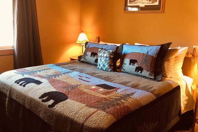 Rustic king bed with bedside tables next to window with a view