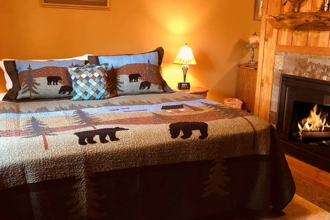 Rustic king bed with bedside tables in  front of the fireplace