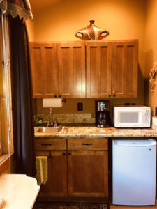 Kitchen cabinets with uppers and lowers, microwave, coffemaker and fridge