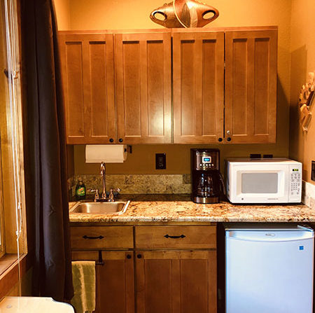 Kitchen cabinets with uppers and lowers, microwave and fridge