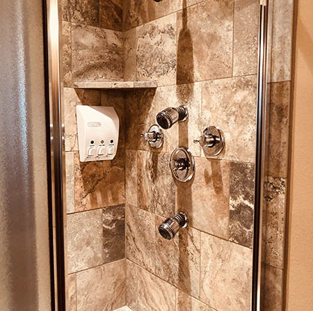 Standing shower with full glass door, low mid and high body showerheads