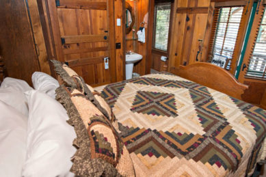 rustic wood panelled room with two large glass paned french doors out to deck and additional window with blinds in natural light filled room with large bed covered in cream and multicolored quilt with white pedestal sink and round wood framed mirror above