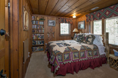 wood panelled room with large rustic log bed and burgundy, olive green and light blue quilt in front of double window with matching valance, window on far wall next to floor to ceiling bookcases