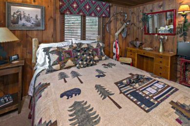 wood panelled room with large log tree bed with pine tree and bear quilt in creams , greens and gray in gront of window with matching window treatment, desk on side wall with red framed mirror above and tv on small side wooden red table