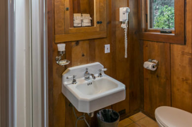 rustic wood panelled bathroom with white sink and turn of the century chome handles with wooden framed medicine chest above and small windo on side and hairdryer on wall