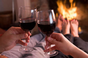 couple with red wine glasses in front of roaring fire